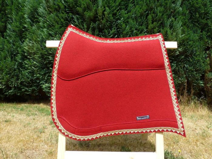 Diese Schabracke ist aus leuchtend rotem Wollfilz gefertigt und mit einer goldenen Posamente verziert.