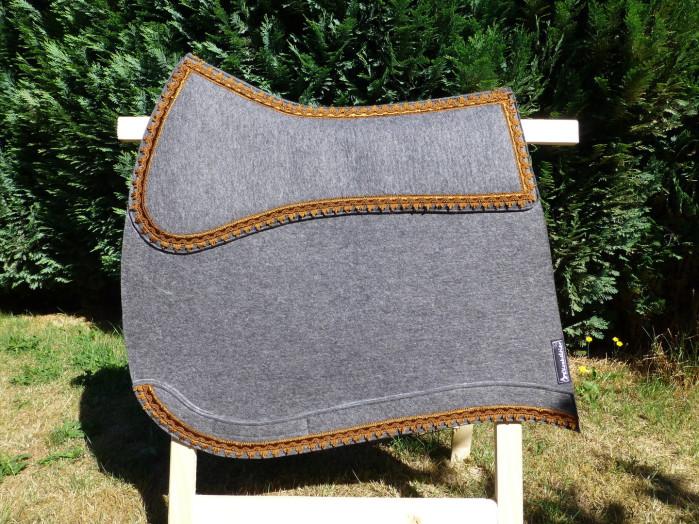 Hier eine Schabracke aus grauem Wollfilz mit bronzefarbener Posamentenverzierung.