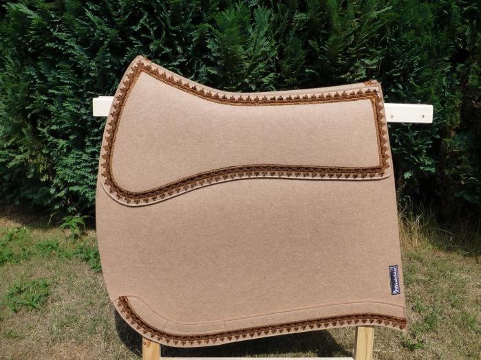 Diese handgearbeitete Schabracke aus reinem Wollfilz in einem Sandbeige wurde mit bronzefarbener Posamentenverzierung veredelt.