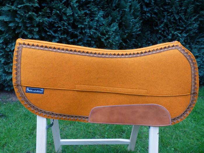 Ein Westernpad aus orangefarbenem Wollfilz mit bronzefarbener Psamentenborte. Als Vario-Pad ist es umpolsterbar.